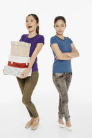 Woman carrying a stack of gift boxes while another woman stares with arms crossed