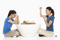 Woman cheering after winning a game of chess