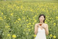 Woman enjoying a cup of tea at the rape field