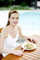 Woman enjoying her meal by the pool side