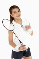 Woman holding a badminton racket and a water bottle