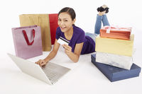 Woman holding a credit card while using laptop