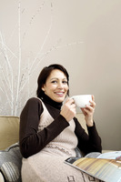 Woman holding a cup of coffee with magazine on her lap