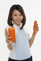 Woman holding a glass of carrot juice
