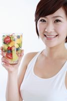 Woman holding a glass of mixed fruits