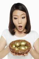 Woman holding a nest filled with gold eggs, looking shocked