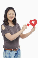 Woman holding a puzzle piece from a heart shape