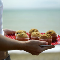 Woman holding a tray of muffins
