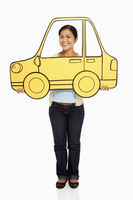 Woman holding up a cardboard car