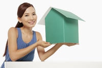 Woman holding up a cardboard house