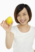 Woman holding up a lemon
