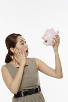 Woman holding up a piggy bank