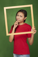 Woman holding up a wooden frame, contemplating