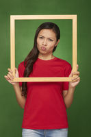 Woman holding up a wooden frame, pouting