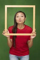 Woman holding up a wooden frame, puckering her lips