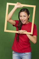 Woman holding up a wooden frame, smiling