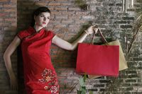 Woman in cheongsam carrying shopping bags