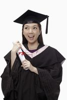 Woman in graduation robe holding her diploma scroll