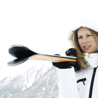 Woman in hooded jacket holding skis