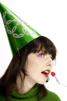 Woman in party hat eating cherry