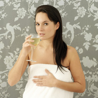 Woman in towel drinking a glass of wine