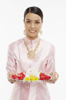 Woman in traditional clothing holding up a tray with thai flower garlands