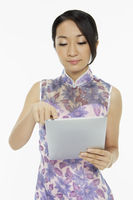 Woman in traditional clothing using a digital tablet