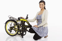 Woman kneeling beside a folded bicycle