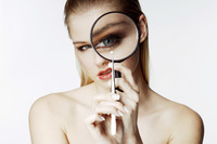 Woman looking at a tiny object with a magnifying glass