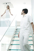 Woman looking at her boyfriend walking down the staircase
