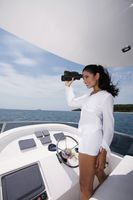 Woman looking through binoculars on yacht