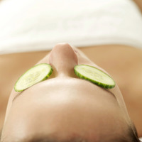 Woman lying down with sliced cucumbers covering her eyes