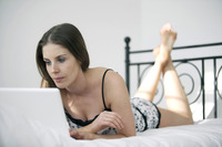 Woman lying forward on the bed using laptop
