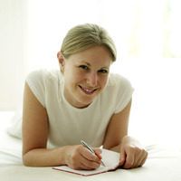 Woman lying forward on the bed writing journal