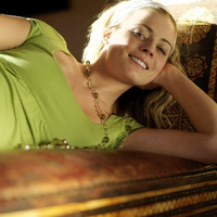 Woman lying on the couch smiling at the camera