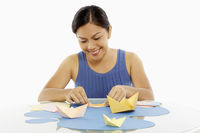 Woman making paper boats