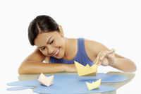 Woman playing with paper boats
