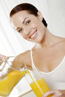 Woman pouring orange juice into a glass