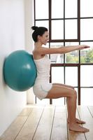 Woman pressing fitness ball against the wall