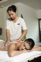 Woman receiving back massage with coconut scrub