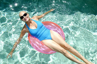 Woman relaxing on inflatable ring in the swimming pool