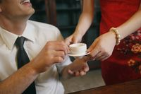 Woman serving businessman with a cup of tea