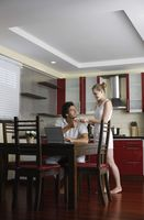 Woman serving man a cup of coffee, man using laptop
