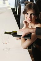 Woman sitting at the bar, wine being poured into her glass