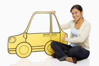 Woman sitting beside a cardboard car, showing hand gesture
