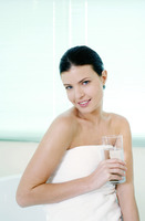Woman sitting on the bathtub corner holding a glass of water