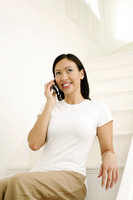 Woman sitting on the staircase talking on the mobile phone