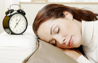 Woman sleeping beside an alarm clock