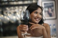 Woman smiling and holding a glass of red wine