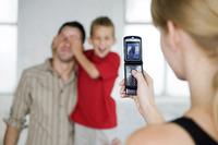 Woman snapping picture for her husband and son